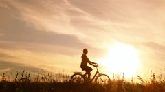 Young woman cycling bike in countryland area over sunset sky background Stock Footage