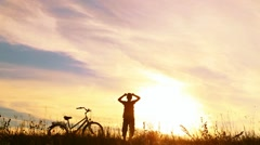 Silhouette of little jumping happy kid near his bike Stock Footage