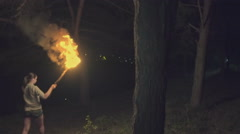 Girl with a fiery torch in his hand goes through the forest at night. Slow Stock Footage