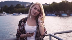 Blonde girl is listening to music by the sea shore. Girl puts on the headphones Stock Footage