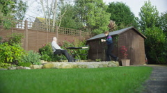 4K Mature couple of retirement age spend time together sitting in their garden Stock Footage