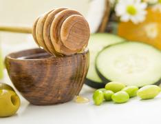 Honey dipper on bowl, olives, peas and slices of cucumber Stock Photos
