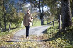 Austria, Salzburger Land, Maria Alm, Mature woman walking on autumn alley Stock Photos
