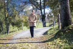 Austria, Salzburger Land, Maria Alm, Mature woman walking on autumn alley Stock Photos