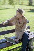 Austria, Salzburger Land, Maria Alm, Mature woman sitting on bench and using Stock Photos