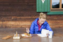 Austria, Salzburger Land, Maria Alm, Mature woman reading book during lunch Stock Photos