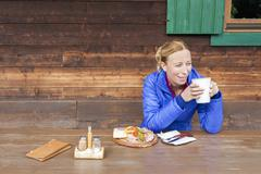 Austria, Salzburger Land, Maria Alm, Mature woman drinking coffee at wooden Stock Photos