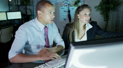 4K Businessman and businesswoman working late at night in a room full of compute Stock Footage