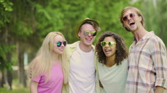 Young joyful friends joking and laughing, having good weekend in park, relax Stock Footage