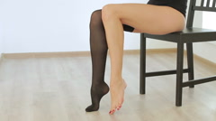 Young beautiful girl slowly puts on stockings Stock Footage