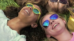 Close-up of friends faces, happy girls and guys lying on grass, joking, laughing Stock Footage