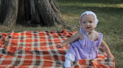 A baby girl sitting on a blanket and holding a stick Stock Footage