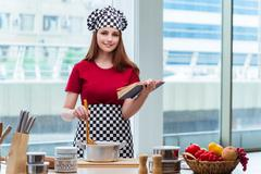 Young housewife referring to recipe book Stock Photos