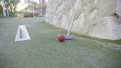 Red mini golf ball and stick leaning on rock 4K Stock Footage