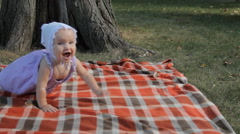 A baby girl smiling and crawling over a blanket Stock Footage