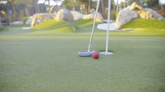 Mini golf red ball and stick leaning beside hole closeup 4K Stock Footage