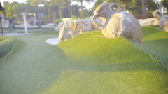 Mini golf course with ball and stick leaning beside hole 4K Stock Footage