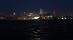 New York city skyline at night. City lights reflects on the water Stock Footage