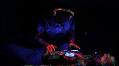 DJ controls, painted with a fluorescent powder on the body of a naked girl Stock Footage