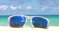 Vacation Travel Concept sunglasses on the sandy beach Stock Footage