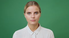 Close up young blonde woman in white shirt looking straight, green screen bac Stock Footage