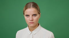 Close up young angry woman in white shirt, green screen background Stock Footage