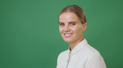 Close up young smiling woman in white shirt half - turned, green screen backg Stock Footage