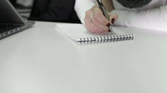 Woman's hands writing on a paper. Woman is taking notes on a pad. Stock Footage