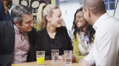 4K Happy group of friends or business colleagues chat together in a small cafe Stock Footage