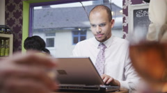 4K Attractive mixed race young professional male working on his laptop in a cafe Stock Footage