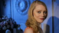 Young slim smiling blonde with diamond earrings and ring standing in night room Stock Footage
