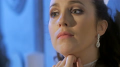 Close-up of sad young beautiful brunette, touching her diamond earring, smiling Stock Footage