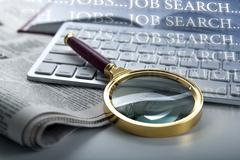 Inscription job search and a magnifying glass Stock Photos