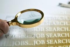 Inscription job search and a hand holding a magnifying glass Stock Photos