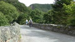 Senior people walking on old arch bridge Stock Footage
