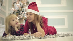 Mother and daughter in red dresses lie on the floor. Stock Footage