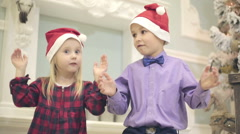 Small girl in red dress and small boy sit on a carpet and clap hands. Stock Footage