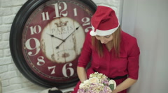 Woman in Santa hat with flowers in her hands sitting near big clock. Stock Footage