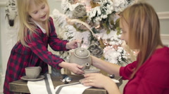 Mother and a small daughter preparing and drinking tea near Christmas tree. Stock Footage