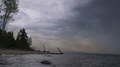 Smoke wafts above rippling lake following forest fire Stock Footage