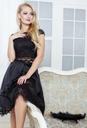 Stylish elegant blonde woman in beauty rich interior, wearing black dress Stock Photos