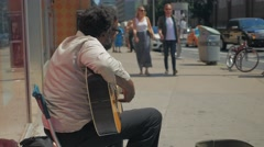 Black Male Street Busking Playing Guitar Pedestrians Walking By Side Stock Footage