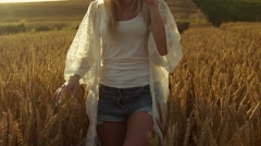 Smiling blond girl wonders cross the field of wheat, woman of fashion, the sun Stock Footage