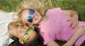 Two beautiful women lying on green lawn, talking, enjoying holidays outdoors 4k or 4k+ Resolution