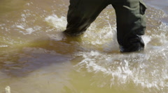 Man trudges through flooded field Stock Footage