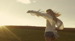 Beautiful girl is running to the sunset, waving her blouse. Stock Footage