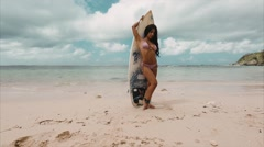 Sexy, beautiful brunette girl, awkwardly posing with surf board. Stock Footage