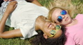 Two female friends lying on grass, gossiping about guys and smiling, friendship 4k or 4k+ Resolution