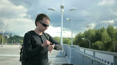 Male cyclist on the road stopped to communicate on a smart watch. He dictated a Stock Footage