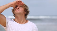 Portrait, male surfer squinting against the sun, against the sea. Stock Footage